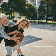 older person playing basketball with a younger person